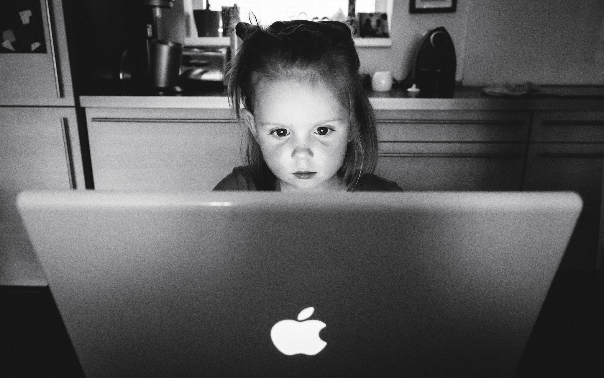 Five-year-old girl browsing a glowing laptop.