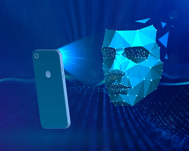 An abstract face composed of many triangles illuminated by a smartphone.